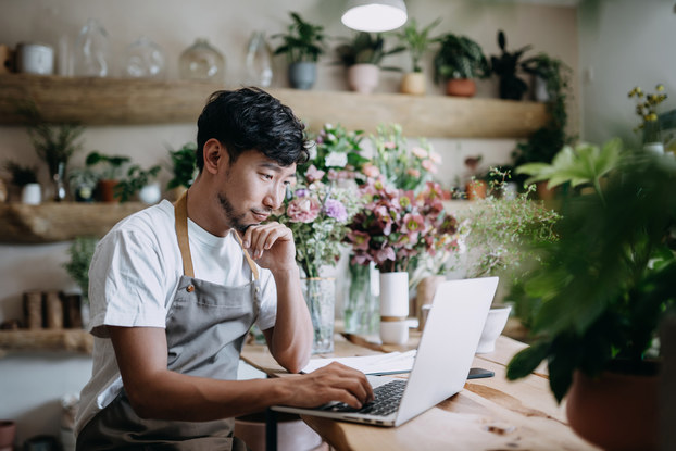 Male florist, owner of small business flower shop, working on laptop over counter against flowers and plants.