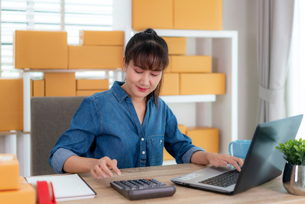 A woman sits at a wooden desk and uses a calculator with her right hand. Her other hand rests on a laptop. In the background are shelves of boxes.