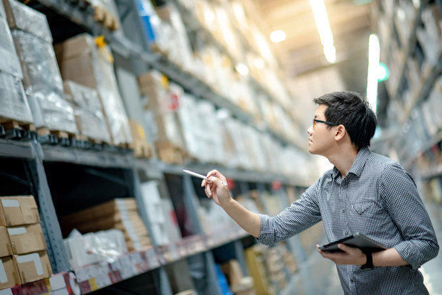 A young man in a button-up shirt stands in a cavernous warehouse, looking up at one of many industrial shelves holding wrapped boxes on wooden pallets. He holds an electronic tablet in one hand and uses the other hand to point a pen at the boxes, as if counting them.