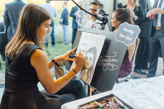 Artist in black dress creates caricature drawing with black marker