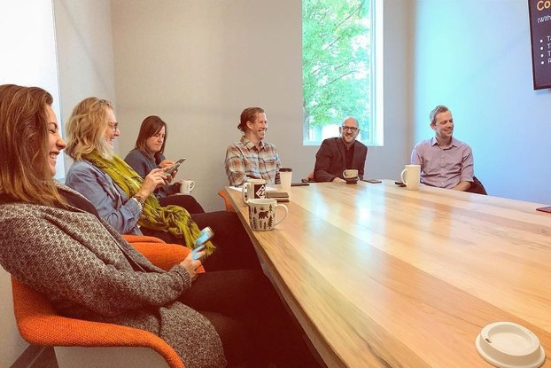 Smiling colleagues have an informal meeting in a conference room