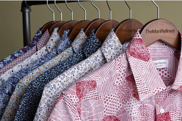 Multi-colored men's dress shirts hang on clothing rack