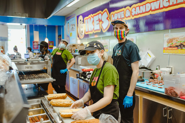 Employees working inside a location of Ike's Love & Sandwiches.