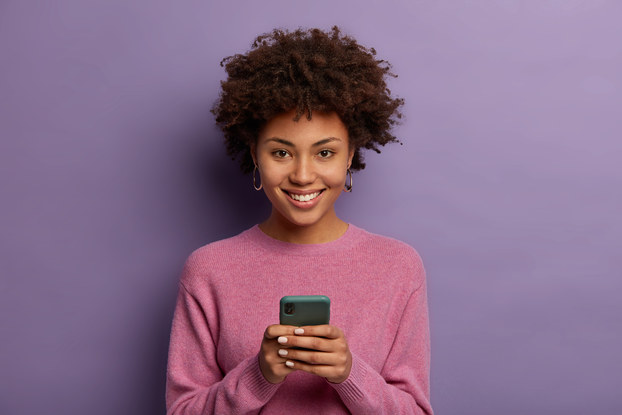 Woman standing on phone in front of a purple background.
