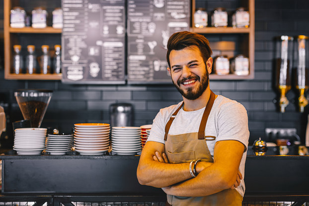 A man wearing a khaki apron stands smiling with his arms folded in front of a counter at a cafe and menu board at a cafe. The menu board is white text on a black background and is mounted on a wall between shelves of jars and carafes. The counter is stacked with plates of various sizes.