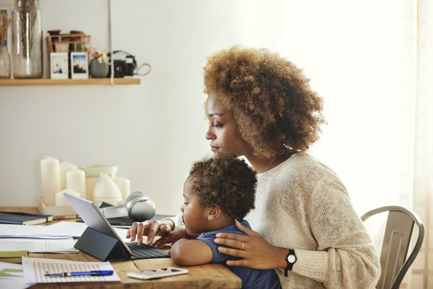 A woman sits at a table scattered with papers and works on a smart tablet with an attached keyboard. Her child, a toddler, is seated in her lap.