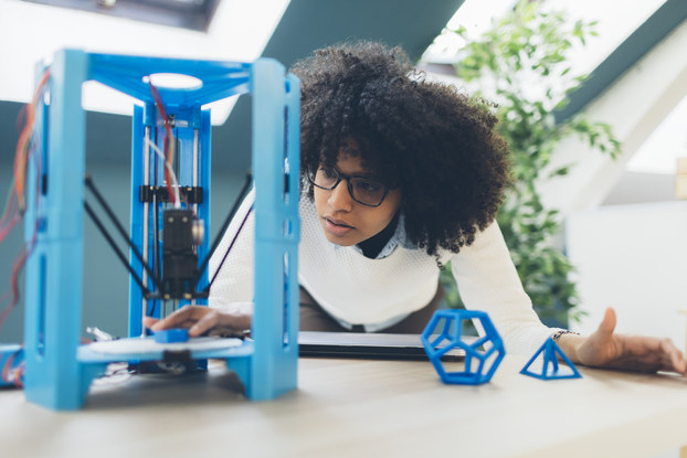 Person working in office, leaning over desk and 3D printer.
