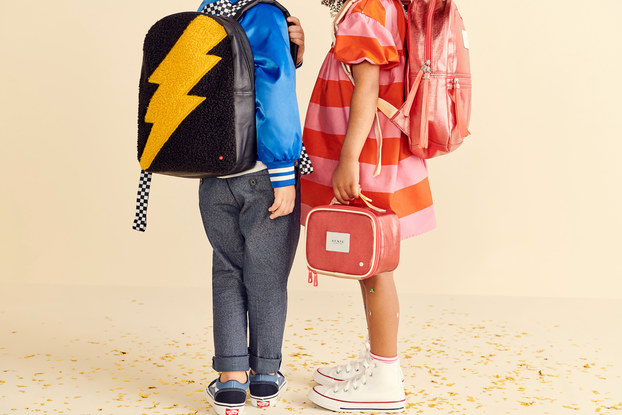 Two children wearing backpacks and holding a lunchbox from STATE Bags.
