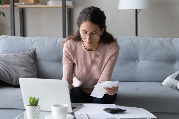 Serious business woman wearing glasses in living room, managing business expenses.