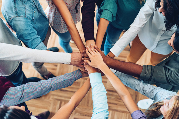 Eleven arms of various skin hues and wearing shirt sleeves of various lengths extend into the center of a circle, where they stack on top of one another in a gesture of camaraderie.