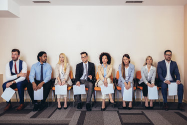 A row of people of many ethnicities and genders sit in chairs. They are all dressed in business casual wear and each person holds a piece of paper.