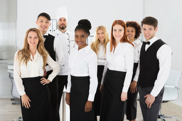 A group of restaurant workers of various ethnicities and genders stand in a group and smile at the camera. They are all wearing variations on a uniform of a white dress shirt and black pants, with some people also wearing a black bow tie and black vest. The only exception is a bearded chef in the back, who wears a white chef's jacket and hat.