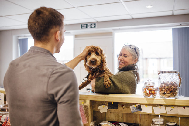 Woman holding her dog at the groomer while the employee pets him.