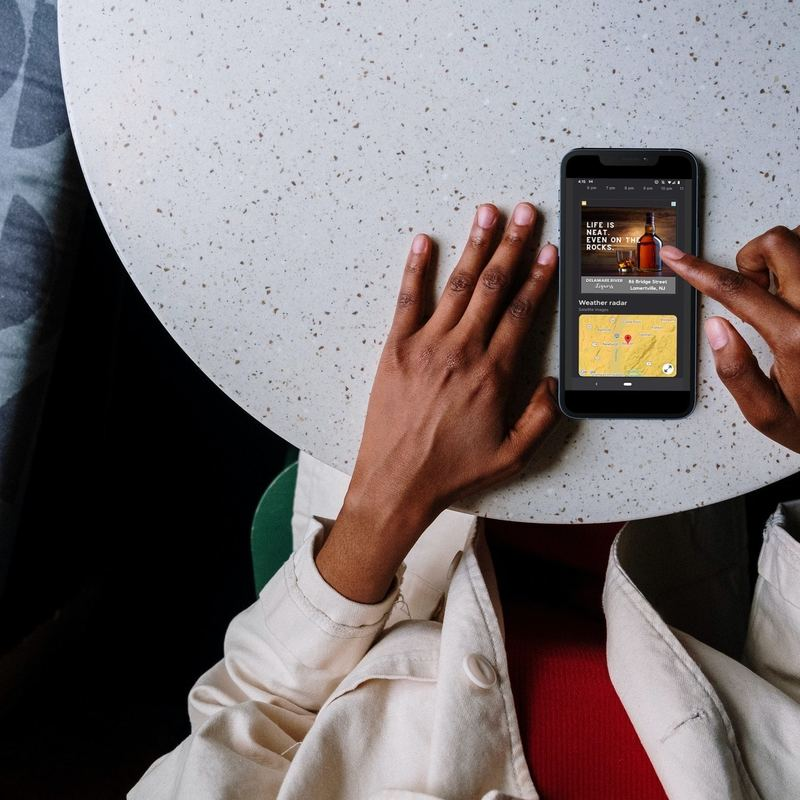 Person looking at digital 3x3 ad on smartphone.