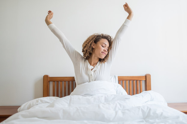 Woman stretching while waking up in bed.