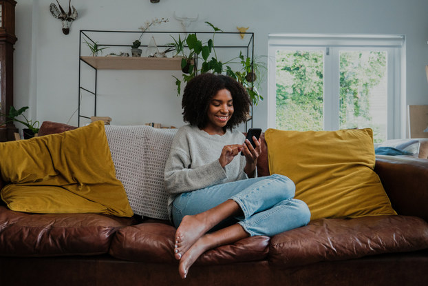 Woman on couch texting on smartphone.