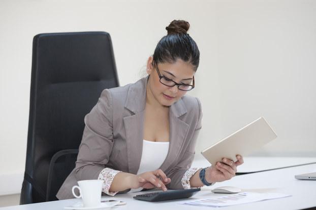 Businesswoman calculating finances at office desk.