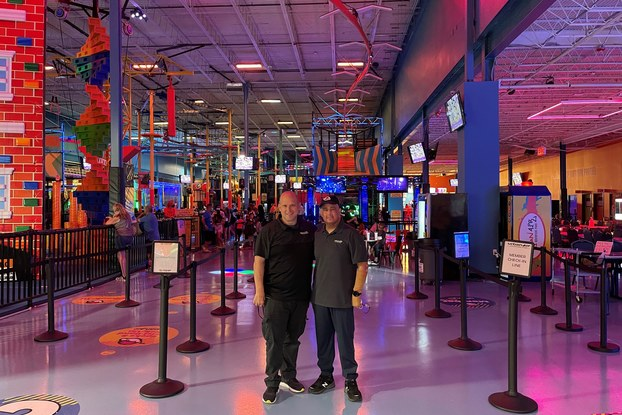 Two men stand next to each other inside an entertainment facility with crowd-control barriers and neon lights