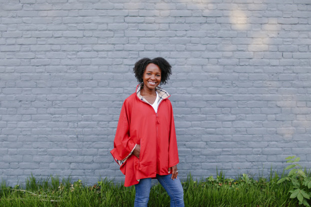 Woman smiles as she stands in front of a white brick wall and grass, wearing a dark orange rain jacket.