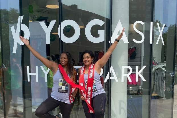 Two women standing in front of a yoga studio in a yoga pose, standing on one leg with one arm stretched over head.
