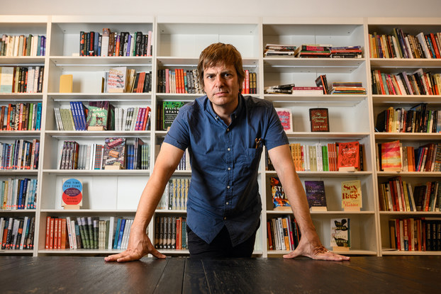 Andy Hunter, CEO, Bookshop.org, in front of bookshelves of books.