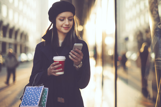 Woman holding shopping bags and coffee and looking at phone.