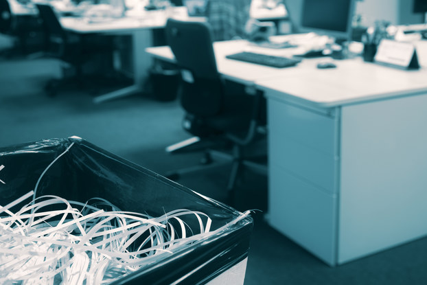 An office with an open floor plan. In the background, out of focus, are rows of desks holding computer monitors and keyboards. In the foreground, in focus, is a trash can filled with shredded paper.