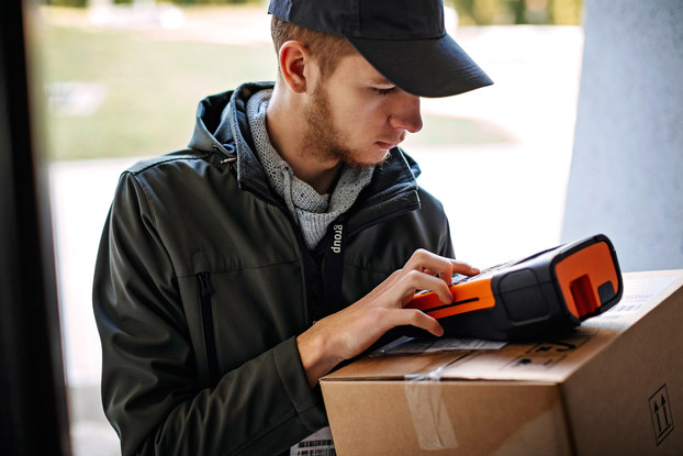 A young man wearing a windbreaker and a baseball cap examines a scanning device, which he balances on top of a package in a brown cardboard box.