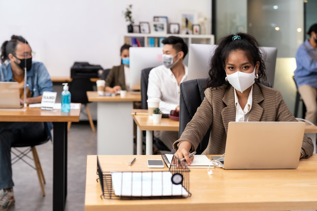 Portrait office employees wearing face mask while social distancing