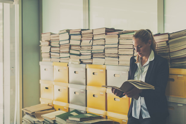 Business woman stands in an office room full of documents in boxes and stacked on top of them.