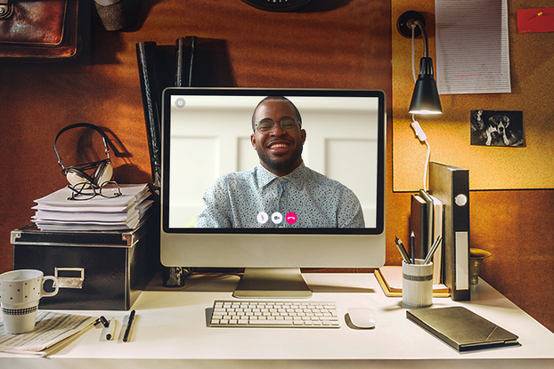 A Talkspace therapist on the screen of a computer monitor that is sitting on the desk of a person's home office.
