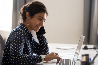 A woman wearing a blue-and-white polka-dotted shirt looks at an open laptop with a smile.