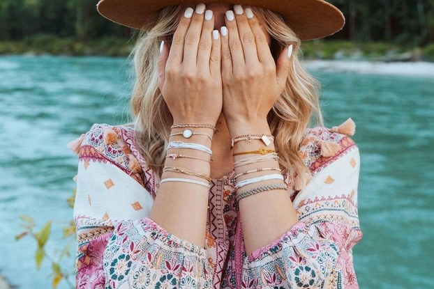 Influencer wearing Pura Vida bracelets and covering her eyes while outside in nature.