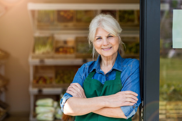An older woman wearing a green apron stands in the doorway of a shop, smiling.