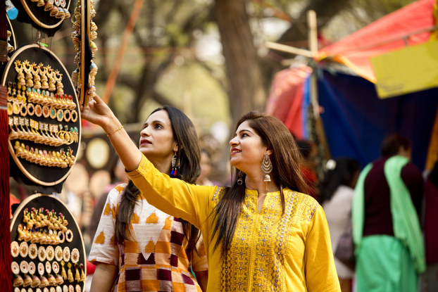 Two women with long dark hair look at hanging displays of large handmade earrings, most of them dangling and gold or copper. The earrings are stuck in circular boards hanging from an unseen structure. In the background are trees and part of a market stall around which other patrons clusters.