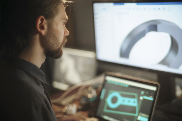 A man, facing away from the camera at an angle, looks at two computer screens. The first screen is on a laptop and shows a black-and-teal-blue design of a key-shaped machine component made up of an open circle attached to a rectangular piece. The second screen sits behind the laptop and is a much larger monitor. It shows a zoomed-in 3D look at the circular part of the component.