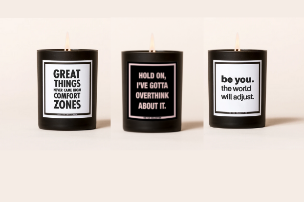 A product image of three candles in black tins, each with a motivational message written in contrasting colors.