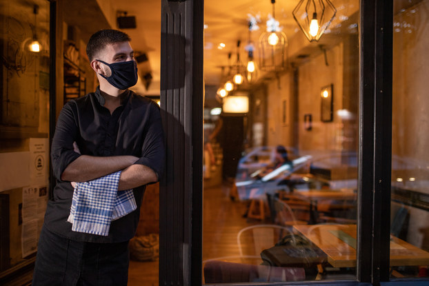 Business owner standing outside restaurant wearing a mask.