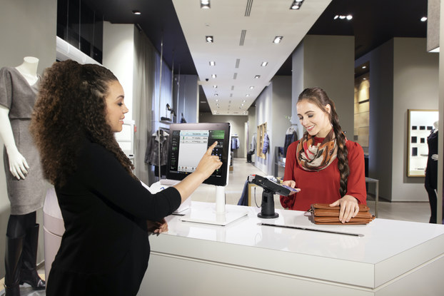 woman checking out with credit card at store