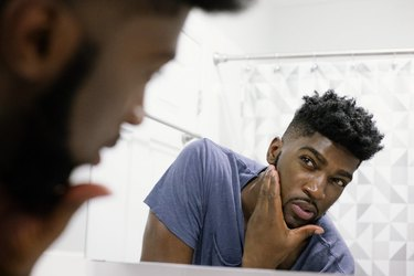 man checking his face in the mirror