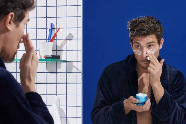 man using eye cream in bathroom mirror
