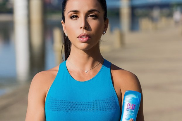 woman dressed in workout clothing holding secret deodorant