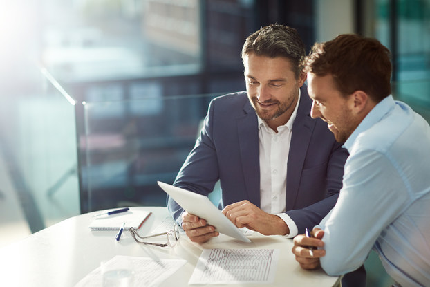 two men in business meeting reviewing paperwork
