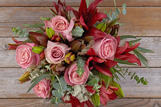 top view of red and pink floral bouquet on wood background