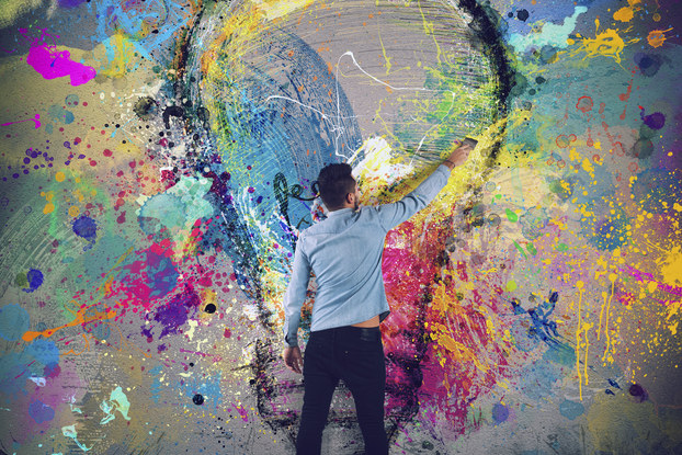 man painting a lightbulb on a wall