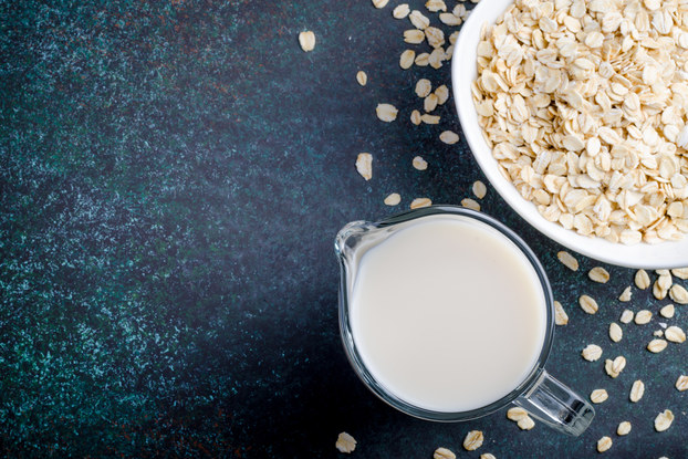 bowl of oats and cup of oat milk on a table