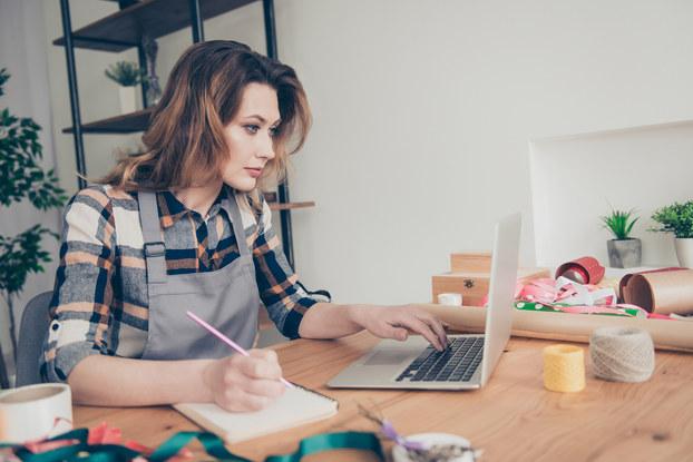 woman on laptop taking notes