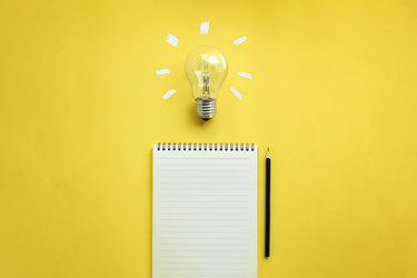 lightbulb and notebook on yellow background