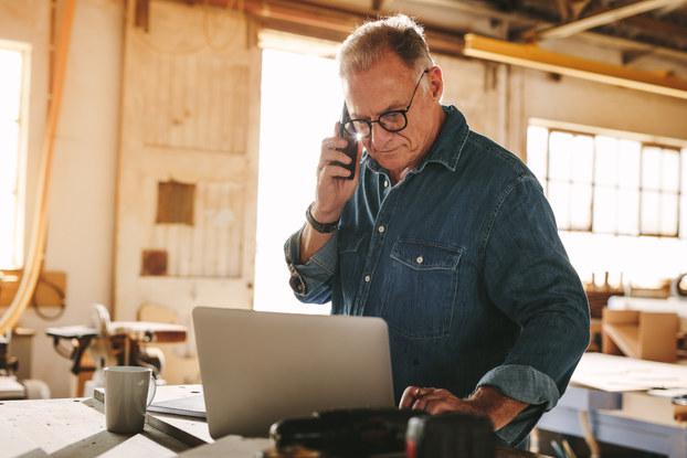Man in demin shirt working on laptop