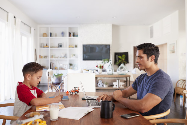 father working at kitchen table with son
